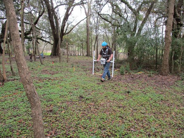 Student operating magnetometry equipment in the field.